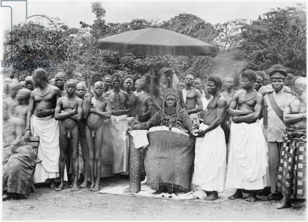 Oba Eweka II seated with a group of men and youths, his right hand on bronze cylindrical object and his left hand held by the official known as the Onobore, c.1920 (inkjet print)