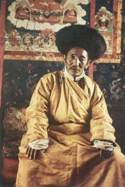 Tendong Shappe in black fox fur hat and gold coloured chuba, Lhasa, Tibet, 1936-37 (colour transparency)