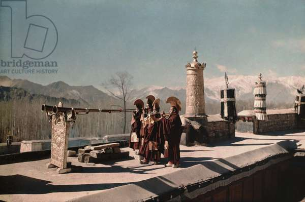 Four Gelugpa monks blowing ceremonial horns on the roof of Kundeling monastery, Lhasa, Tibet, 14th February 1937 (colour transparency)