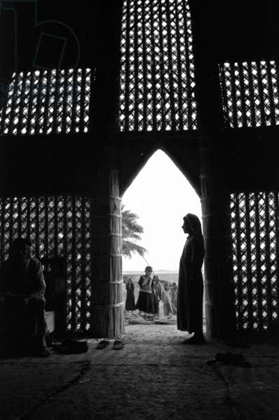 Interior view of the mudhif (guest house) belonging to Mahalhal, with a man standing in the doorway, near Fuhud, Iraq, 1958 (b/w photo)