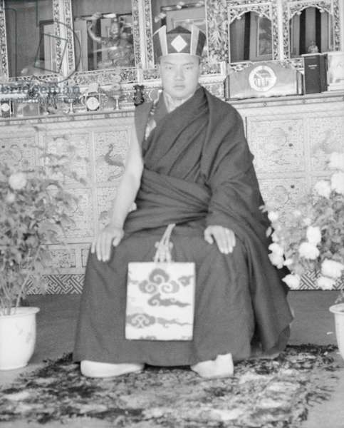 The 16th Gyalwa Karmapa, Rangjung Rigpe Dorje, wearing the black crown (shwa nag) of the Kagyud order of Buddhism at his summer palace at Tsurphu, Tolung Valley, c.1946-50 (b/w photo)
