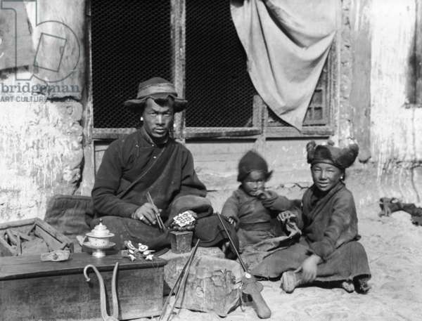 Tibetan silversmith in Lhasa engraving a charm box with his two children, c.1920-21 (b/w photo)