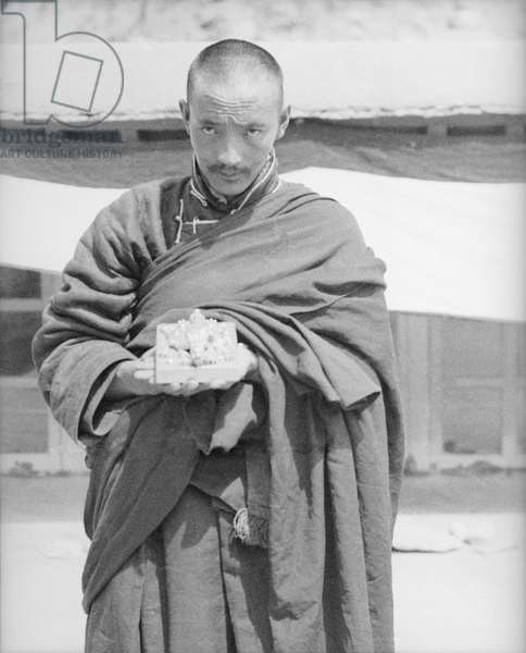 A monk holding out the Tsurphu seal which is decorated with embossed metalwork, Tsurphu Monastery, Tolung Valley, Tibet, 1949 (b/w photo)