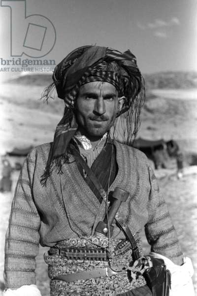 Portrait of a Kurdish man, standing, carrying a knife in his waistband, Halgord, Iraq, August – October 1950 (b/w photo)