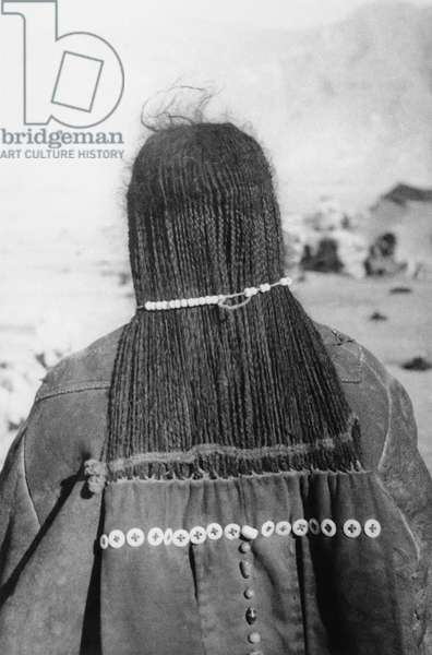 Back view of a nomad woman showing long strip of cloth attached to several thin plaits of hair, Lhasa Area, Tibet, 7th January 1937 (gelatin silver print)