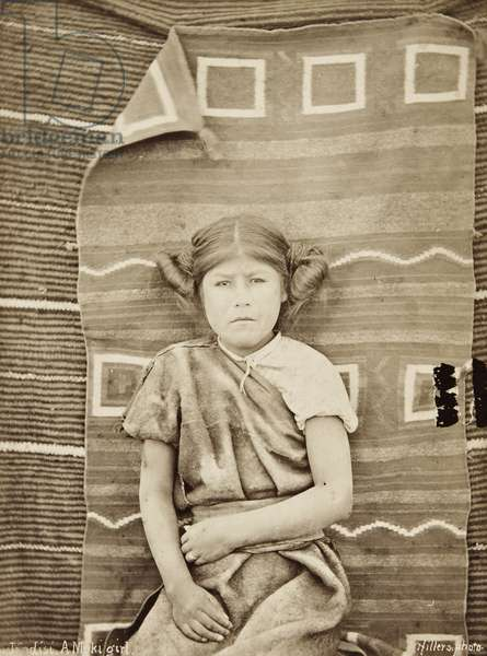 Portrait of a thirteen-year-old Hopi girl named Modisi sitting in front of two Navajo blankets, 1879 (albumen print)