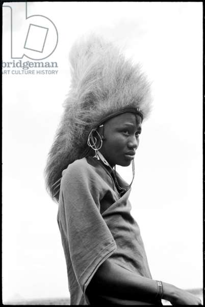 Portrait of a Maasai moran (warrior), standing, wearing a lion's mane headdress, Simanjiro Plain, Tanzania, 1963 (b/w photo)