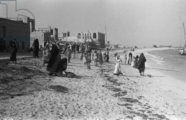View of women on the Corniche in the town of Abu Dhabi, United Arab Emirates, March 14-16, 1948 (b/w photo)