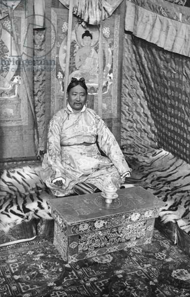 Ringang's elder brother Sonam Rabten, the Minister of Agriculture, sitting on a tiger skin with thangka and auspicious hangings adorning the wall behind him, Lhasa Area, Tibet, 10th-14th January 1937 (gelatin silver print)