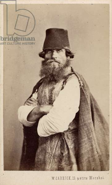 Half length studio portrait of a man wearing a shirt, sleeveless tunic (made of animal skin?), a tall hat and a cape, c.1873 (albumen print)
