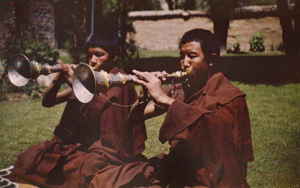 Portrait of two monks, both kneeling on the ground, blowing silver trumpets, Lhasa, Tibet, March 1945 – early 1949 (colour transparency)