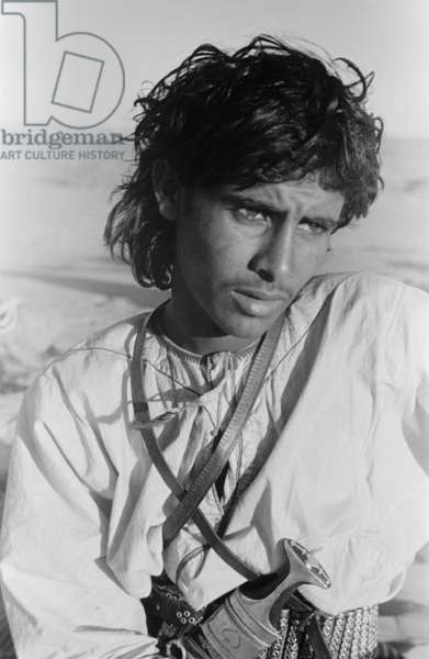 Half length portrait of Salim bin Ghabaisha, one of Wilfred Thesiger's travelling companions, Al Ain, United Arab Emirates, May 1-10, 1948 (b/w photo)