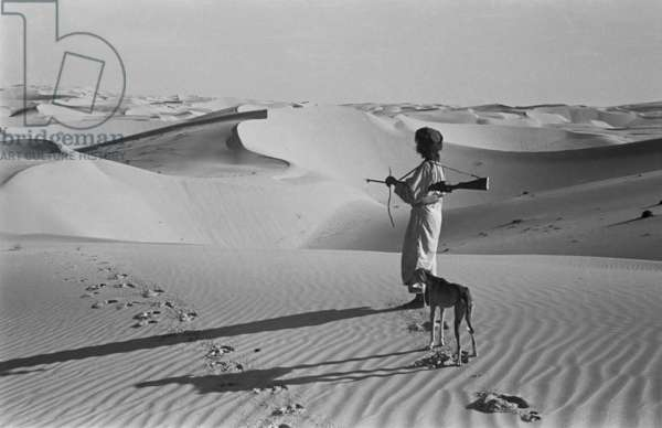 Back view portrait of Salim bin Ghabaisha, one of Wilfred Thesiger's travelling companions, with a saluki in Liwa oasis, United Arab Emirates, November 14–29, 1948 (b/w photo)