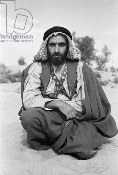 Seated portrait of Sheikh Zayed bin Sultan Al Nahyan resting in the sand in Al Ain, United Arab Emirates, December 20, 1948 – January 27, 1949 (b/w photo)