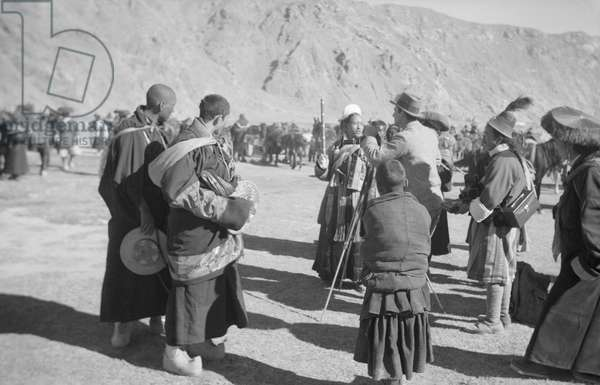 Frederick Spencer Chapman, in the centre of the image, takes a photograph of an official at the ceremony to mark the return of the Reting Rinpoche to Lhasa, Tibet, 23rd November 1936 (b/w photo)
