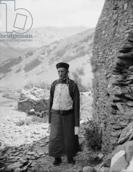 Kusho Palhese standing by wall with view of hills in distance, c.1920-21 (glass plate gelatin print)