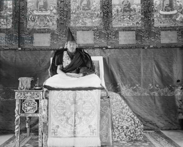 The Thirteenth Dalai Lama seated on a throne on an ornately carved and painted dais in the Norbu Lingka Palace, 14th October 1921 (glass plate gelatin print)