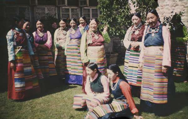 Group portrait of eleven aristocratic Tibetan women, standing and sitting on the ground, wearing colourful silk dresses and aprons, Lhasa, Tibet, March 1945 – early 1949 (colour transparency)