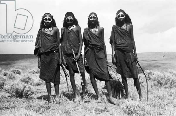 Group portrait of four Maasai youths, standing, carrying bows and blunted arrows, Ngorongoro District, Tanzania, 1961 (b/w photo)