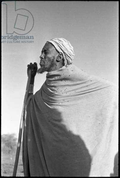 Portrait of a man, a Boran elder, standing, leaning on a staff, with flies covering his face and clothing, Ethiopia, 1959 (b/w photo)