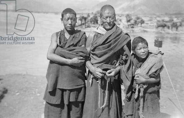 Group of three monks at the river crossing close to the Dekyi Lingka, where the British Mission stayed whilst in Lhasa, Tibet, 6th September 1936 (b/w photo)