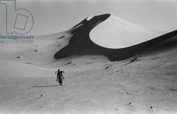 View of Salim bin Kabina, a member of Wilfred Thesiger's travelling party, walking below the crest of a large dune the Empty Quarter (Rub' al Khali), Saudi Arabia, January 12-18, 1948 (b/w photo)