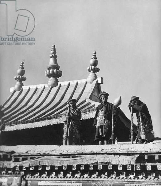 Zimchongpa or foot soldiers in ancient armour on the roof of the Jokhang Temple at dawn, Lhasa, Tibet, 24th December 1936 (gelatin silver print)