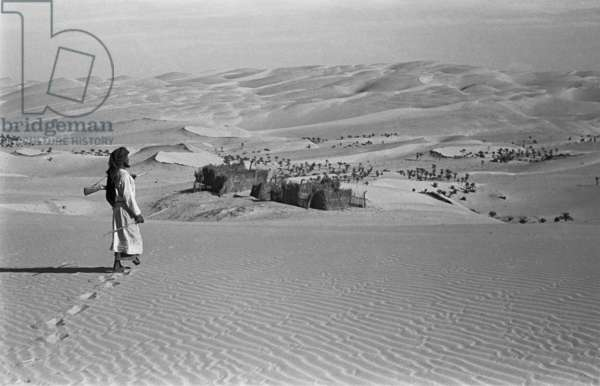 View of a member of Wilfred Thesiger's travelling party at a Bani Yas settlement in Liwa oasis, United Arab Emirates, November 14–29, 1948 (b/w photo)