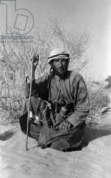 Portrait of Wilfred Thesiger sitting in the Wadi al 'Ayn, Oman, February 8–16, 1949 (b/w photo)