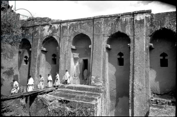 View of the monolithic rock-hewn church of Gabriel at Lalibela, with people processing from its entrance in the foreground, Ethiopia, 1960 (b/w photo)