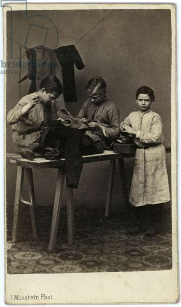 Studio portrait of a three children; two sit on a trestle table and sew clothes, the other leans on a box, upon which is a brush, on the same table.  More items of clothing hang on a line behind them, c.1873 (albumen print)