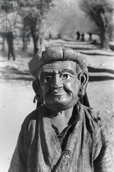 Lhasa mummer in mask representing an Indian Saddhu, close–up, performing in the grounds of the British Mission residency in the Dekyi Lingka, Lhasa, Tibet, 1st December 1936 (gelatin silver print)