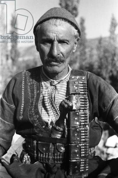 Portrait of an Assyrian man named Jargi Eashu carrying a knife in his waistband, Iraq, May – September 1951 (b/w photo)