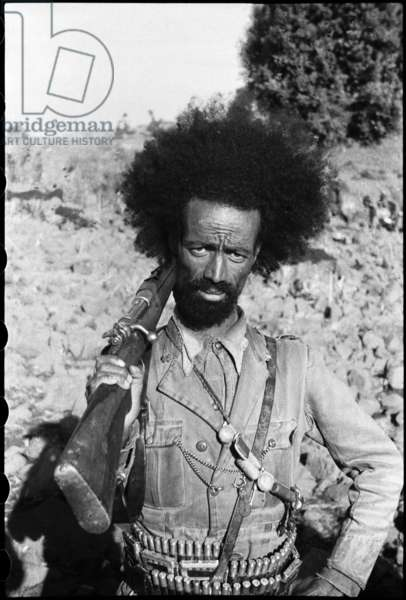 Portrait of a man, an Abyssinian 'Patriot' soldier, standing, holding a rifle over his right shoulder, Agibar, Shewa, Ethiopia, June 1941 (b/w photo)
