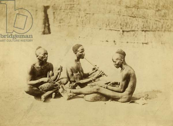 Three Acholi musicians playing harps and flute, 1879 (albumen print)