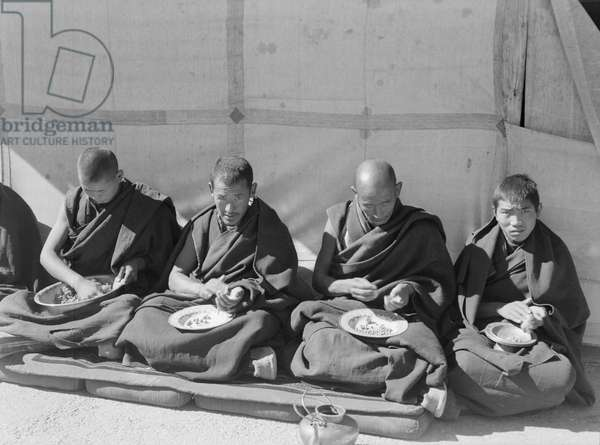 Group of four monks eating in front of a textile awning, Lhasa Area, Tibet, 1936-37 (b/w photo)