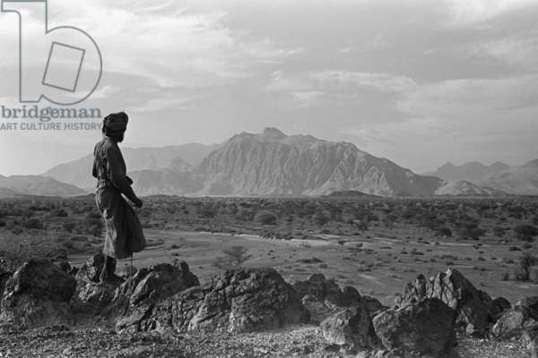 View of a member of Wilfred Thesiger's travelling party looking out across the Wadi Sayfam towards Jebel Kawr, Oman, March 30 – April 2, 1949 (b/w photo)
