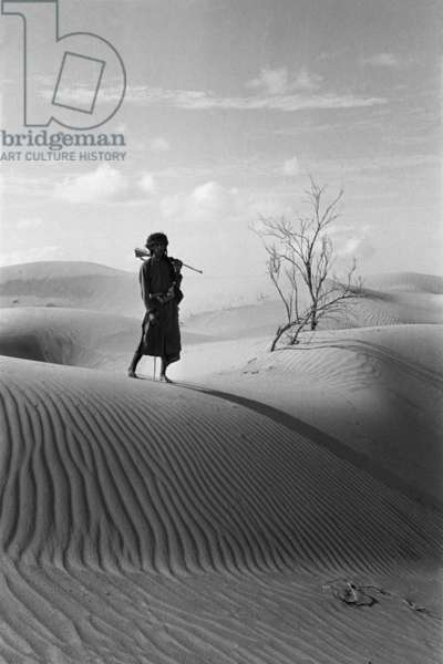 Portrait of Salim bin Kabina, one of Wilfred Thesiger's Bedouin companions, standing on a sand dune in the Ramlat ar Rabbad sands, United Arab Emirates, February 3–12, 1950 (b/w photo)