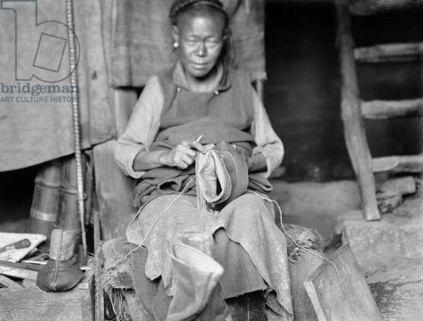 Portrait of a Tibetan cobbler in Lhasa making boots, 1920-21 (negative quarter print)