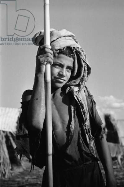 Portrait of a boy, a herder, leaning on a pole, Iraq, 1956 (b/w photo)