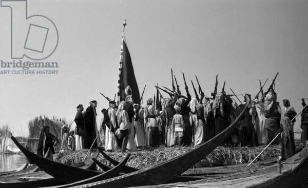 View of a crowd of people of the Fartus tribe, with a flag overhead and rifles raised, dancing the hausa, a tribal war dance, Awaidiya, Iraq, 1956 (b/w photo)