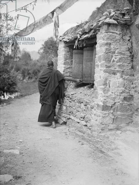 Monk turning prayer wheels enclosed in a chorten on the Lingkhor pilgrimage route around Lhasa, Tibet, 8th September 1936 (b/w photo)