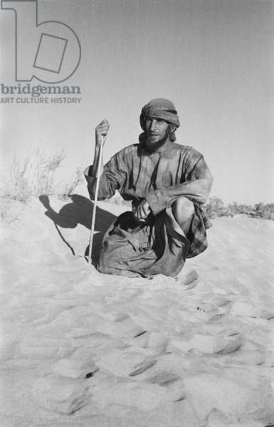 Seated portrait of Wilfred Thesiger, As Saruq, Al Gharbia Region, Abu Dhabi Emirate, United Arab Emirates, March 7-14, 1948 (b/w photo)