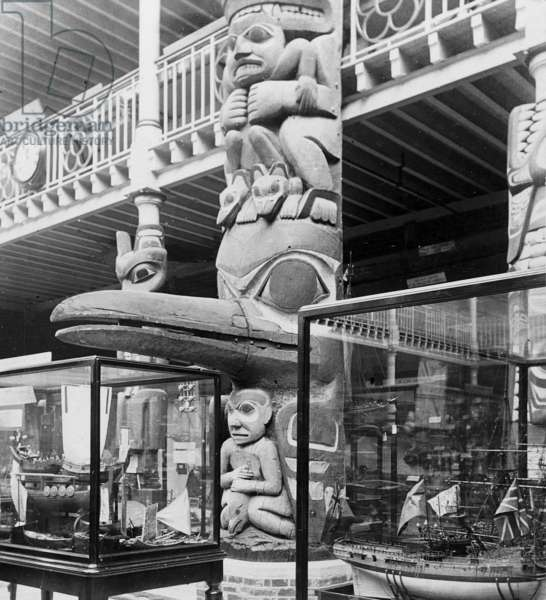 Close up views of display cases and base of the totem–pole in the Court at the Pitt Rivers Museum (b/w photo)