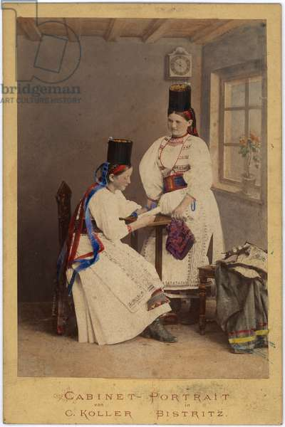 Full length portrait of two women wearing 'traditional' Saxon costume, in a domestic setting, c.1873 (hand-tinted album print)