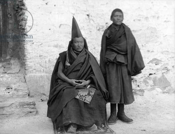 Seated priest, with young boy standing, from hermitage above Gyantse plain, 1904-20 (negative quarter plate)
