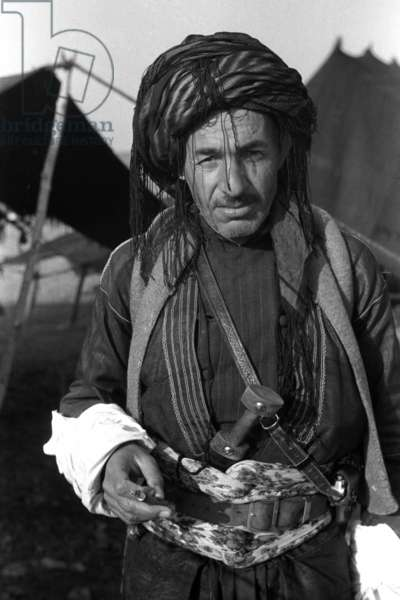 Portrait of a Kurdish man, standing, carrying a knife in his waistband, Iraq, May – September 1951 (b/w photo)