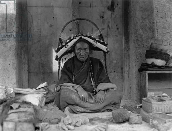 The richest trader in Gyantse sitting at her stall in the market, wearing a headdress and neck ornament of beads, 1920-21 (negative quarter print)