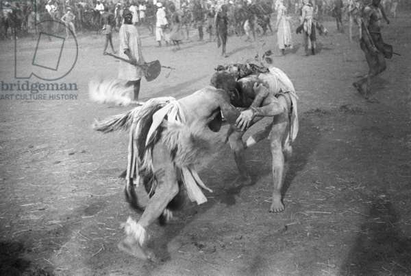 View of two men wrestling during a funeral ceremony, Gharb, Kurdufan, Sudan, 1940 (b/w photo)