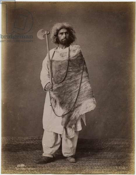 Man carrying an axe wearing a tunic, animal skin and beads, c.1880 (albumen print)